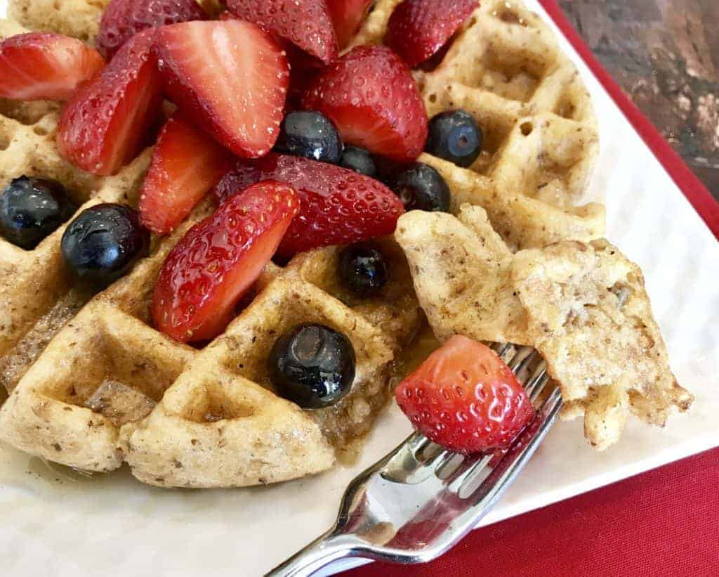 Vegan and Gluten Free Mixed Berry Oatmeal Waffles with Cinnamon Syrup on a plate with mixed berries and a piece on a fork