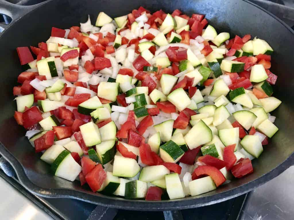 Chopped onion, zucchini, and red bell pepper cooking in pan on stove