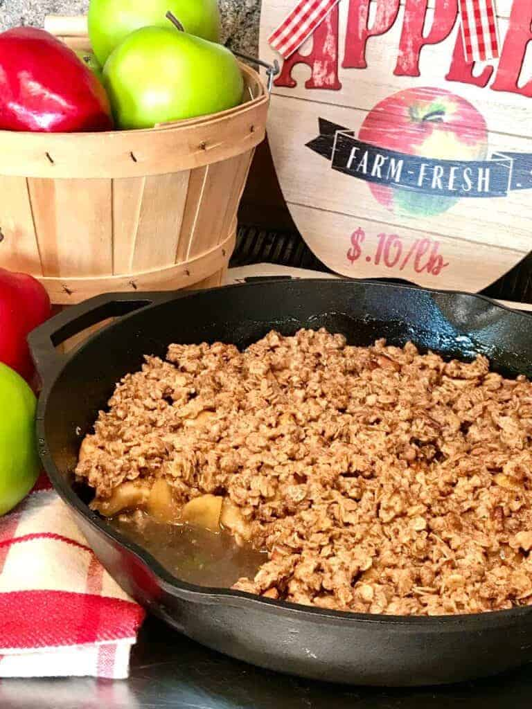 Right of the Oven Apple Crisp in a Cast Iron Pan with Apples in Background