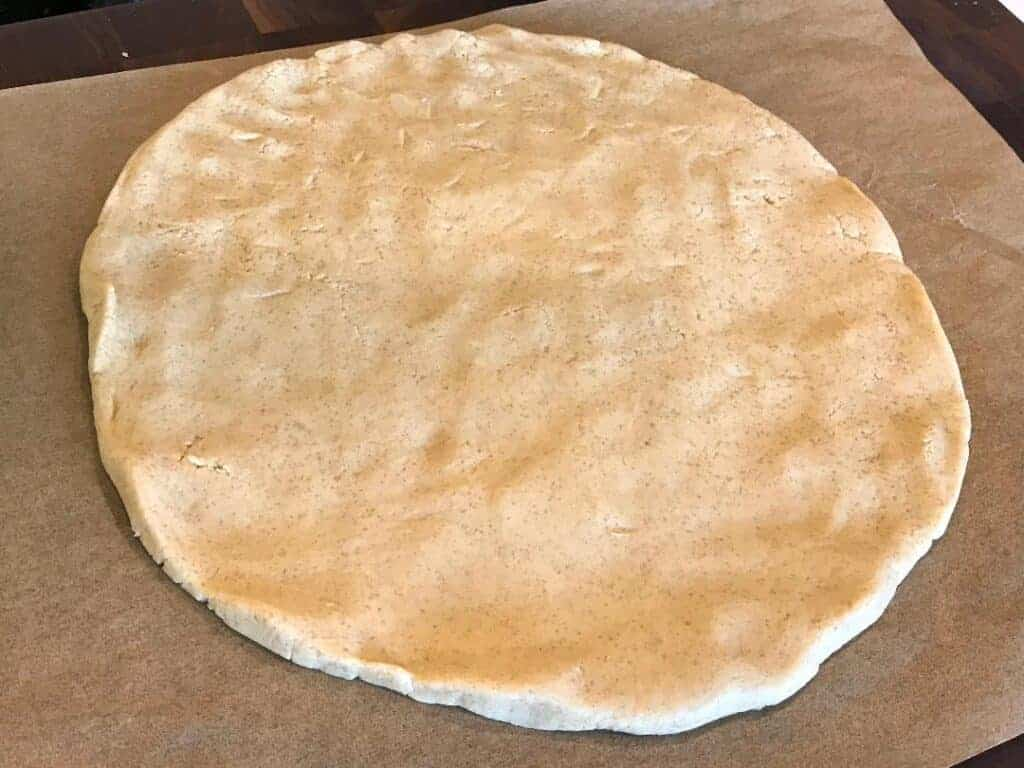 Raw pie crust dough rolled out to a 10 - 12 inch circle, about 1/4 of an inch thick.