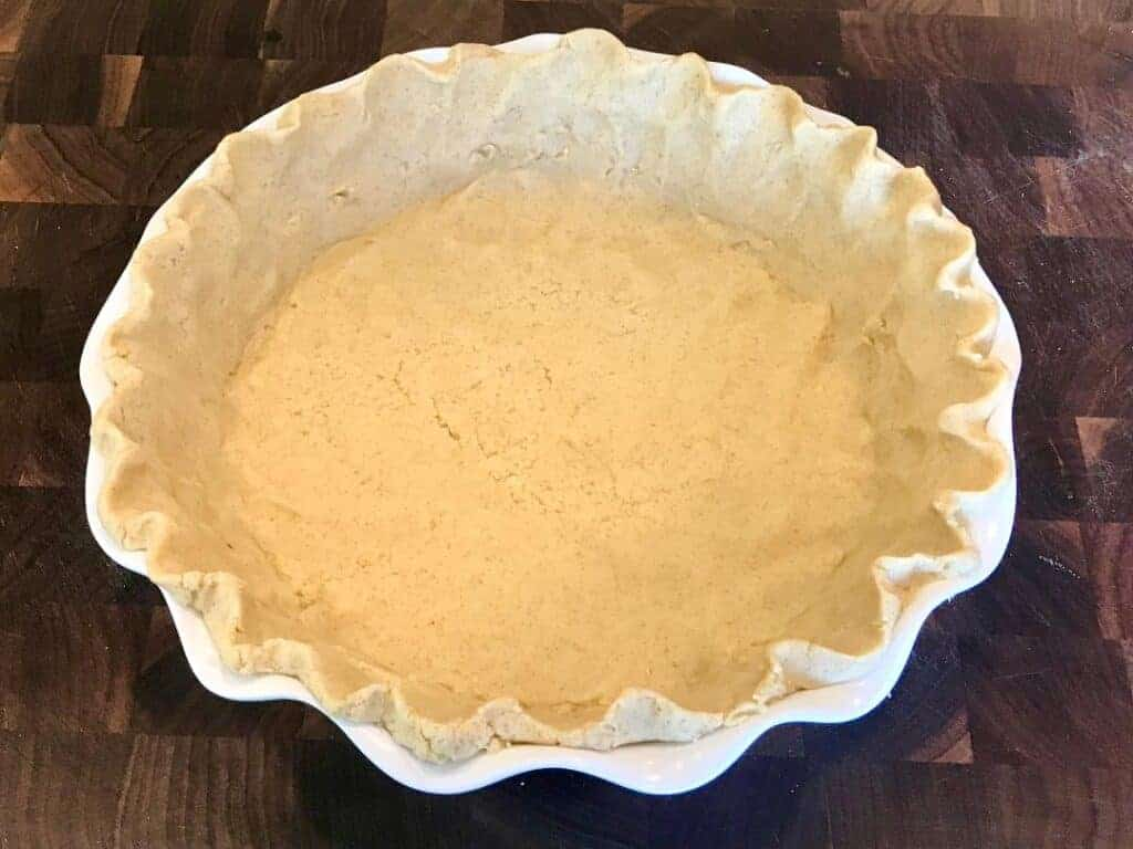 Pie crust dough flattened against the bottom and sides of the pan with the edges crimped.
