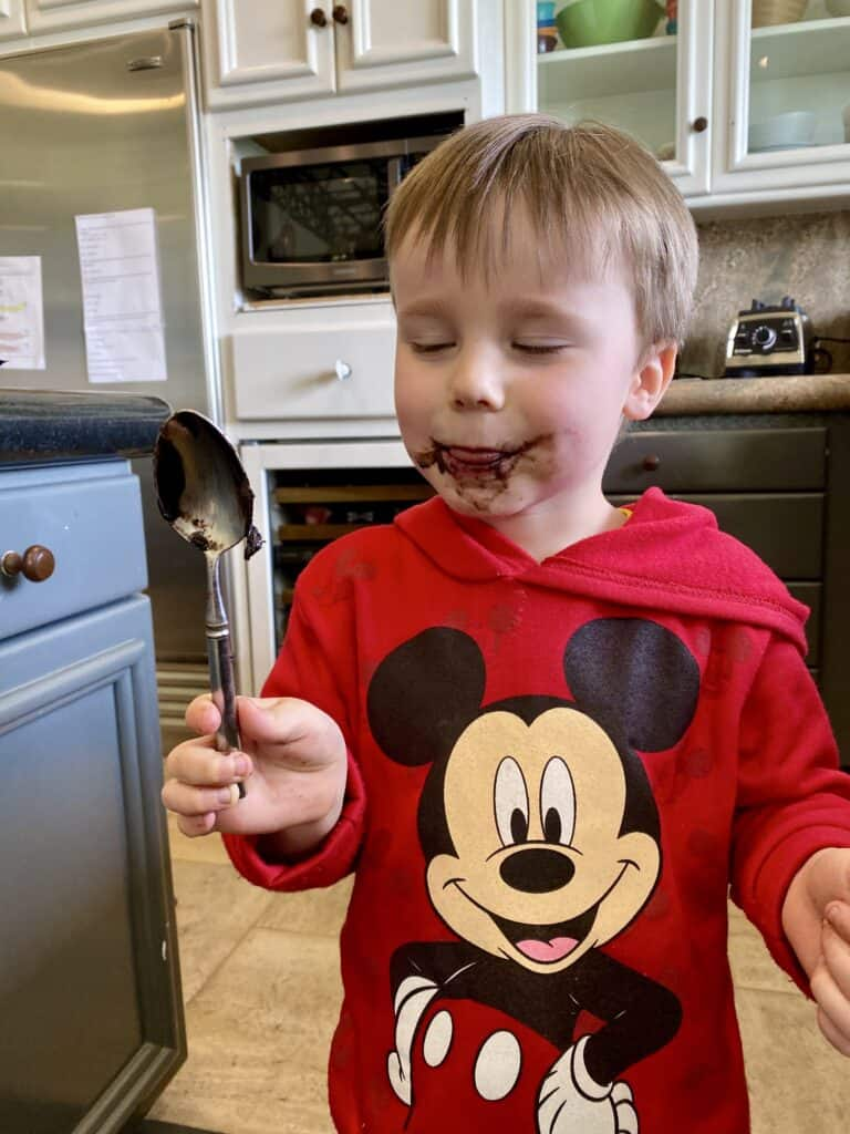 James Dunham licking a chocolate dough covered spoon with chocolate all over his face.