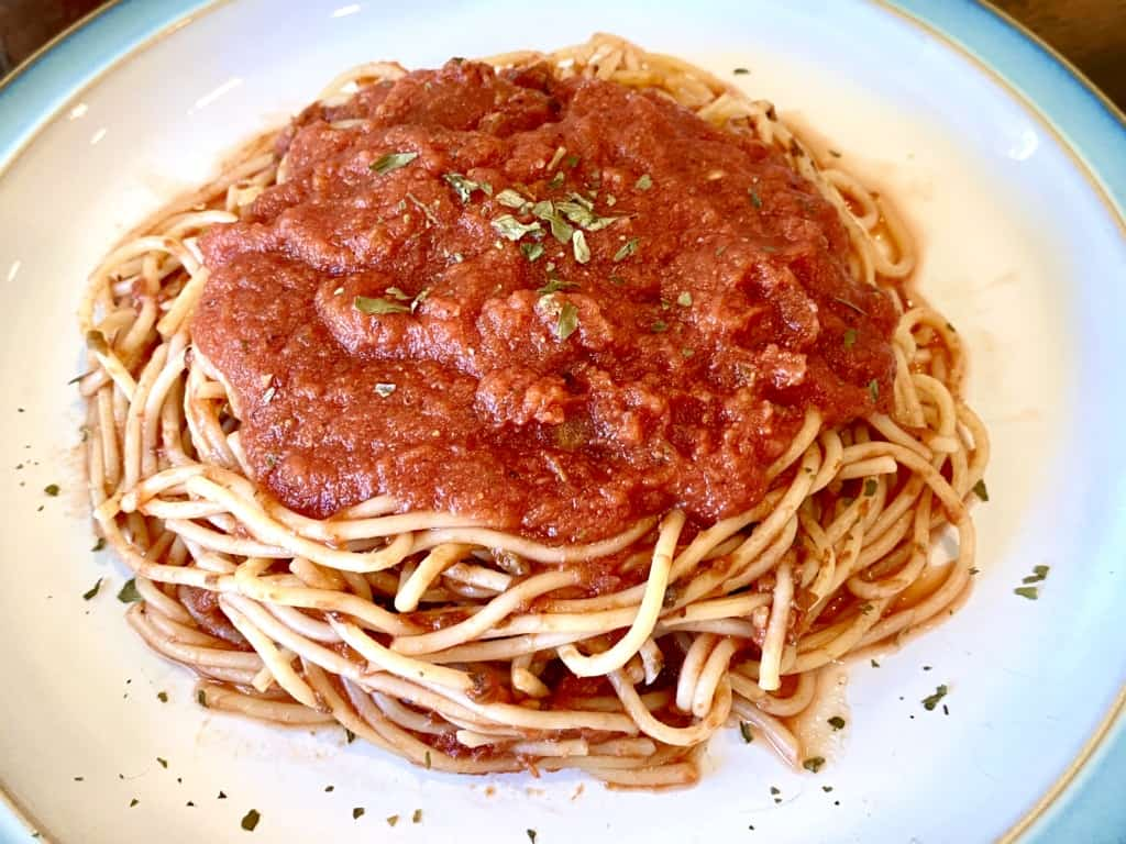 Homemade marinara sauce over a plate of spaghetti noodles.
