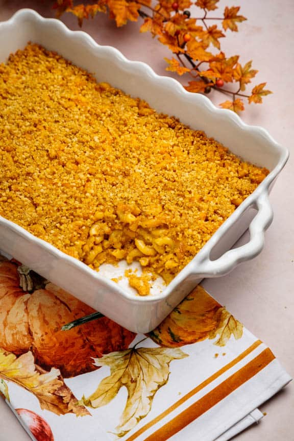 top side view of white casserole dish with baked mac and cheese, scoop taken out of side and fall leaves in background